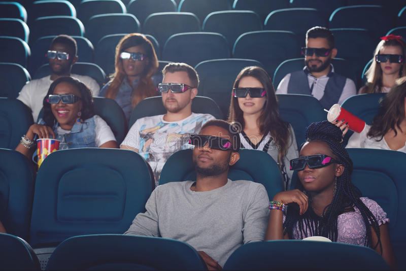 Africans and caucasians watching movie in 3d glasses. Africans and caucasians watching movie in 3d glasses in modern cinema hall. Group of young people eating stock image