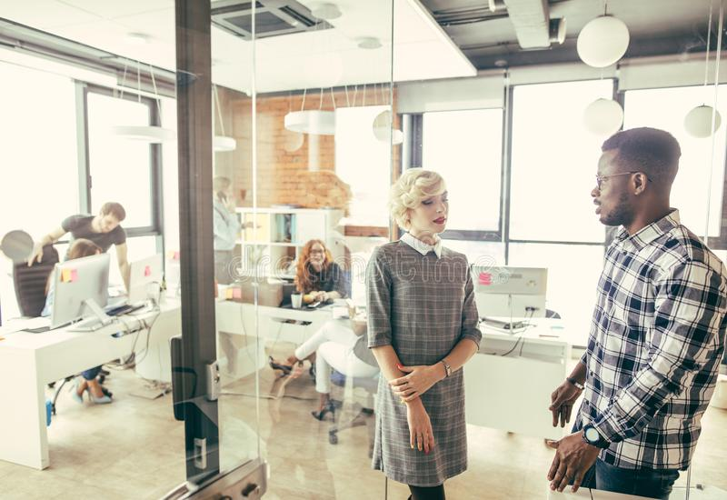 Afrikaan beheert het vertellen van blonde werknemer royalty-vrije stock afbeeldingen