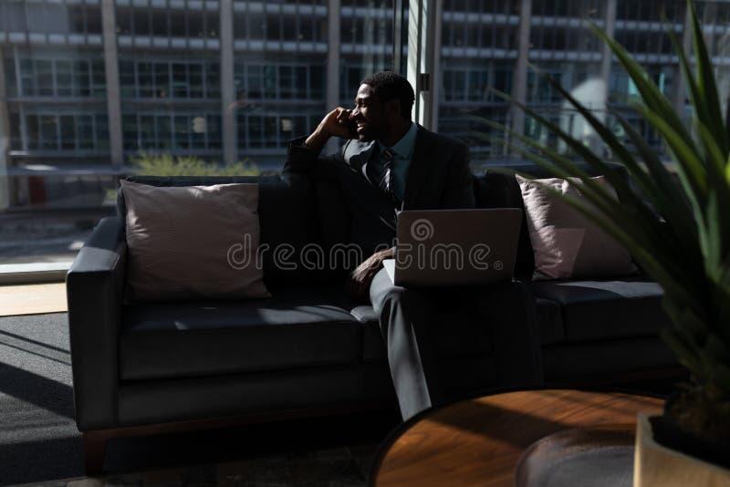 Afrikaans-Amerikaan van zakenman met laptop die op mobiele telefoon op bank in bureau spreken stock fotografie