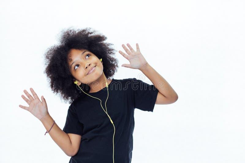 Afrikaans Amerikaans afrojong geitje die de muziek met oortelefoons luisteren - royalty-vrije stock foto