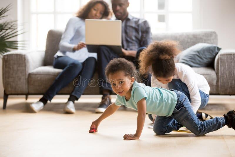 Afrikaans Amerikaans echtpaar die laptop met behulp van terwijl de kinderen spelen stock afbeeldingen