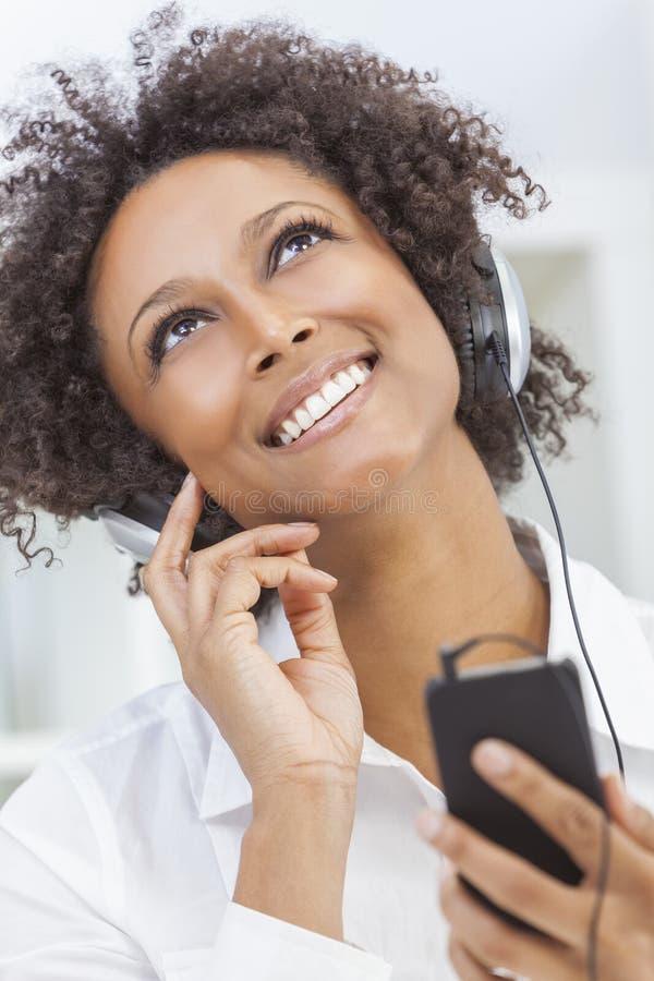 Afrikaans Amerikaans Meisje die aan MP3 Spelerhoofdtelefoons luisteren royalty-vrije stock afbeelding