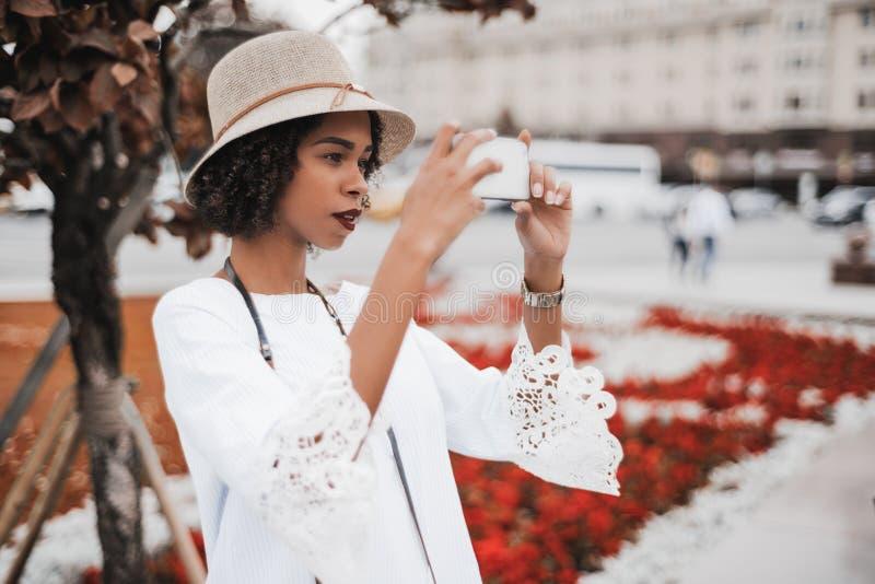 Afrikaans-Amerikaans meisje die foto's op straat via celtelefoon nemen stock fotografie