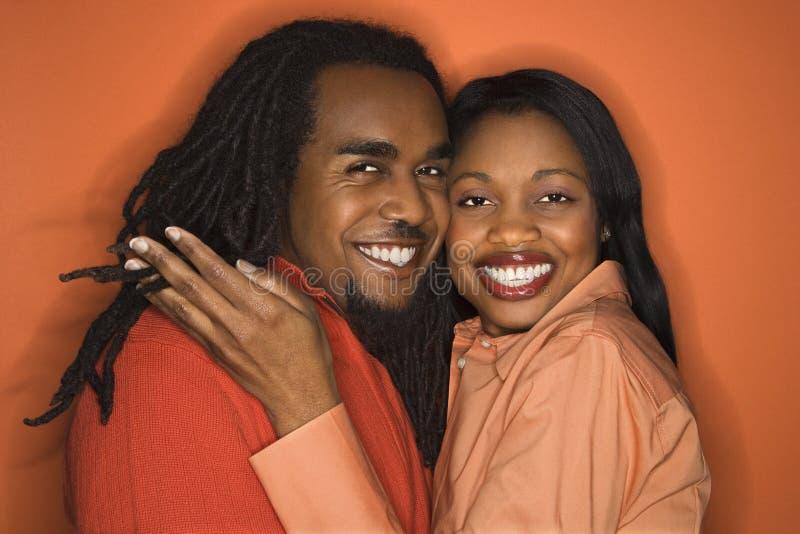 Afrikaans-Amerikaans paar dat oranje kleding op sinaasappel draagt backgr stock afbeeldingen