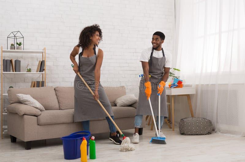 Afrikaans-Amerikaans paar die karweien thuis samen doen stock afbeelding