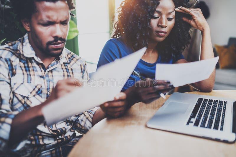 Afrikaans Amerikaans paar die rekeningen controleren samen bij de houten lijst Jonge zwarte mens en zijn meisje die laptop met be stock foto