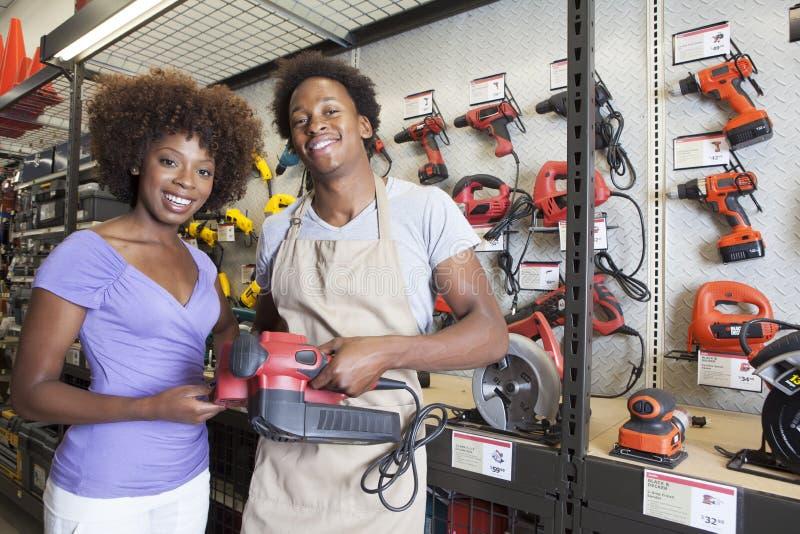 Afrikaans Amerikaans vrouw het kopen hulpmiddel bij ijzerhandel stock foto's