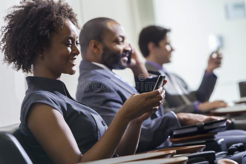Afrikaans Amerikaans Vrouwenmeisje Texting op de Luchthaven van de Celtelefoon stock foto's