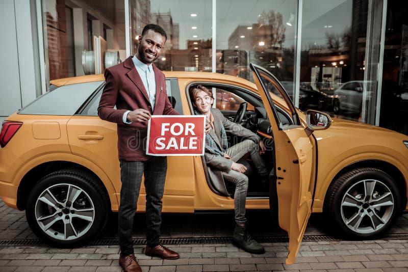 Afrikaans-Amerikaanse afdelingschef die aardige passagiers oranje auto verkopen stock afbeeldingen
