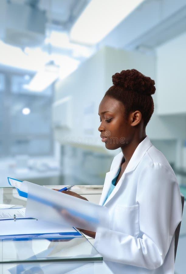 Afrikaans-Amerikaanse biologencontroles die resultaten in scientif rangschikken stock afbeeldingen