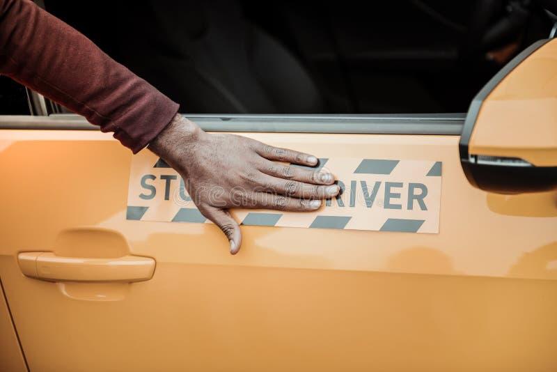 Afrikaans-Amerikaanse drijfinstructeur die zijn student oranje auto tonen royalty-vrije stock foto's