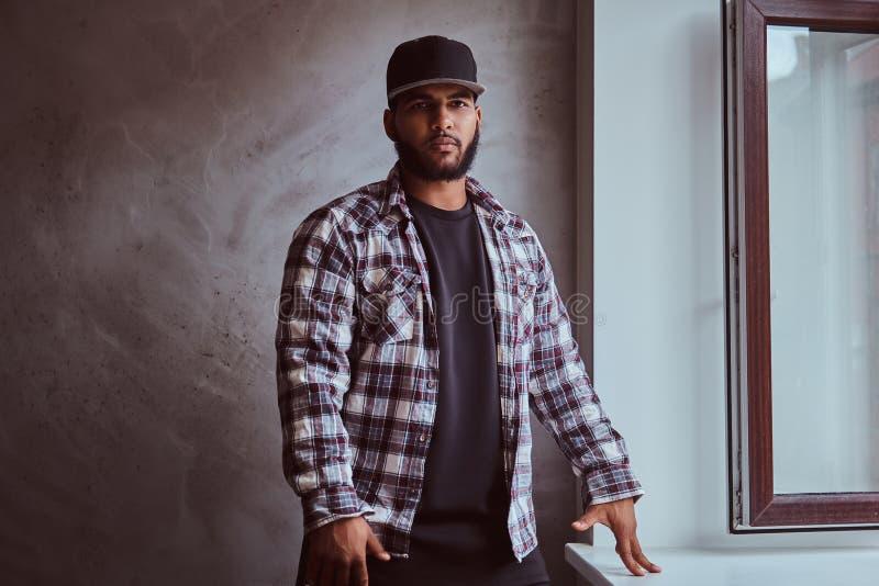 Afrikaans-Amerikaanse gebaarde mens die een geruit overhemd en een GLB dragen die zich naast venstervensterbank bevinden royalty-vrije stock afbeeldingen