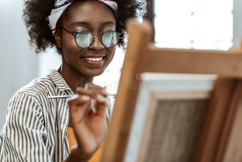 Afrikaans-Amerikaanse kunstenaar die terwijl ge?nspireerd en opgewekt gevoel glimlachen stock afbeeldingen