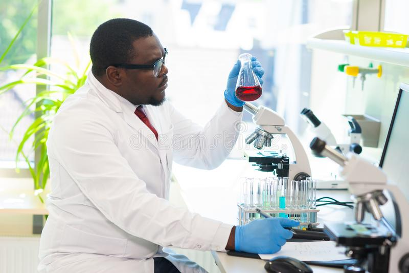 Afrikaans-Amerikaanse medische arts die in onderzoeklaboratorium werken Wetenschapsmedewerker die farmaceutische experimenten mak stock afbeeldingen