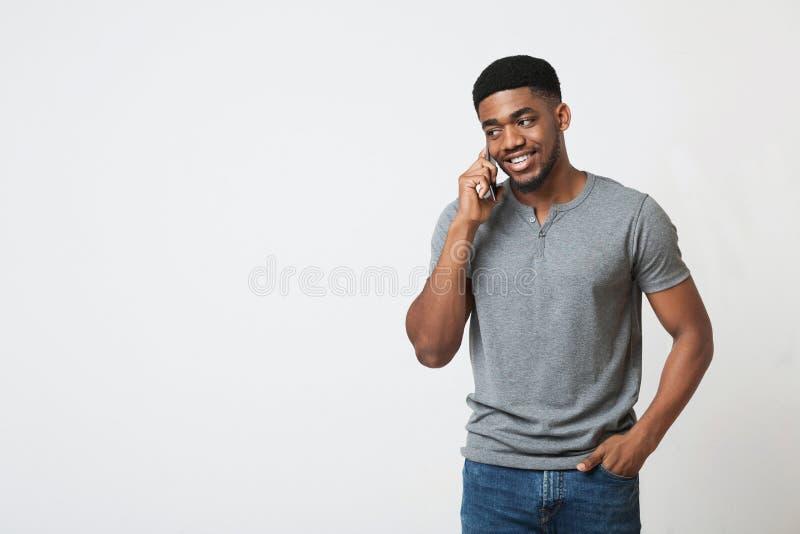 Afrikaans-Amerikaanse mens die bij mobiele telefoon en het glimlachen spreken royalty-vrije stock afbeelding