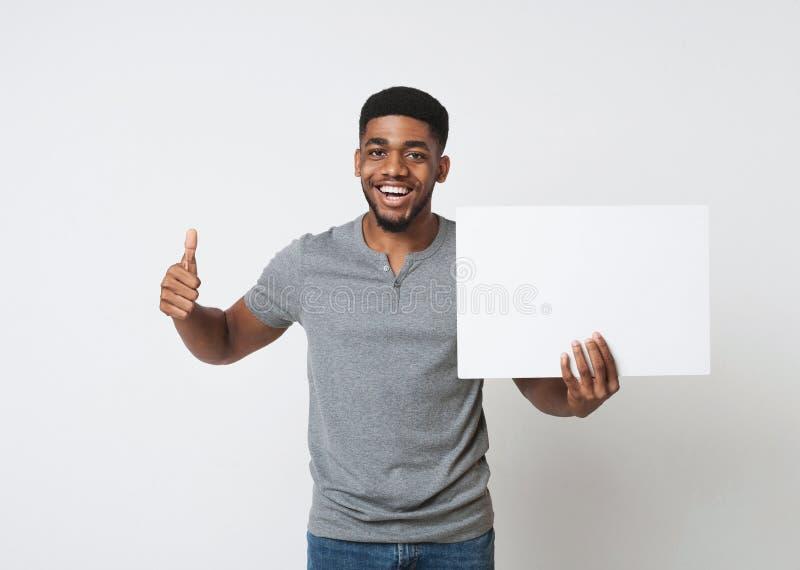 Afrikaans-Amerikaanse mens die witte lege raad houden en duim tonen stock fotografie