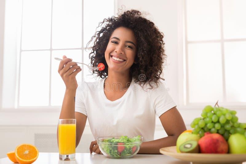 Afrikaans-Amerikaanse vrouw met plantaardige salade en vers sap stock foto's