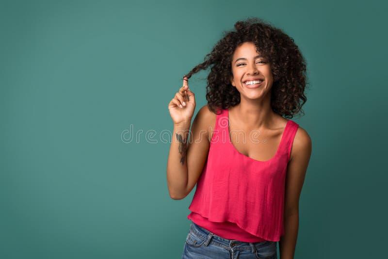 Afrikaans-Amerikaanse vrouw wat betreft haar krullend haar op turkooise achtergrond royalty-vrije stock afbeelding