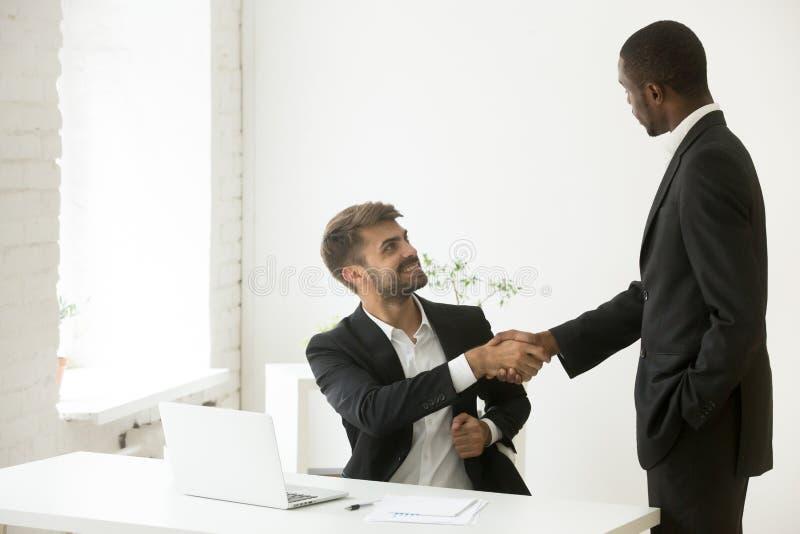 Afrikaans-Amerikaanse werkgever die Kaukasische werknemer met pro gelukwensen stock foto