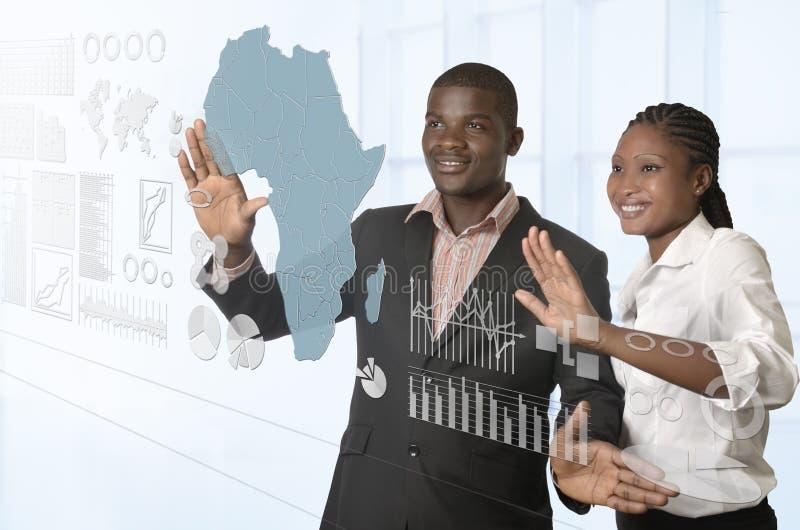 Afrikaans commercieel team die aan virtuele touchscreen werken stock fotografie