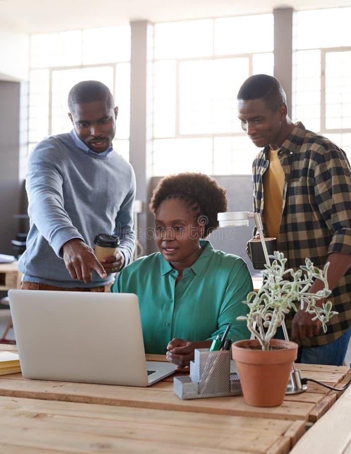 Afrikaans commercieel team die laptop samen in een bureau met behulp van stock foto