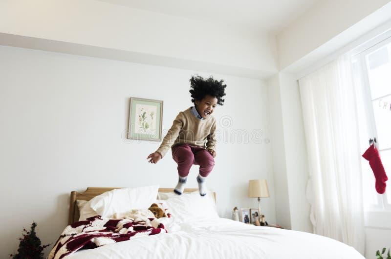 Afrikaans jong geitje die een prettijd hebben die op een bed springen stock afbeelding