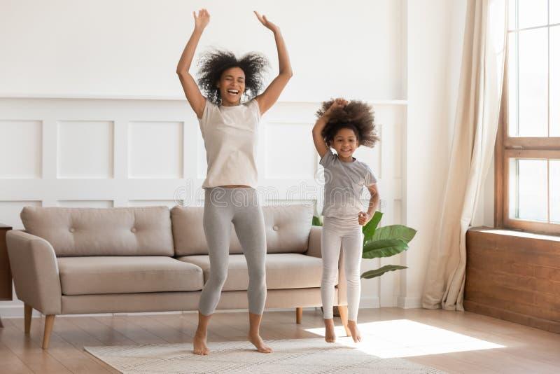 Afrikaans mamma met jong geitjemeisje springen die in woonkamer dansen stock foto's