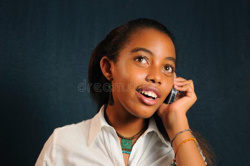 Afrikaans meisje dat celtelefoon met behulp van royalty-vrije stock foto's