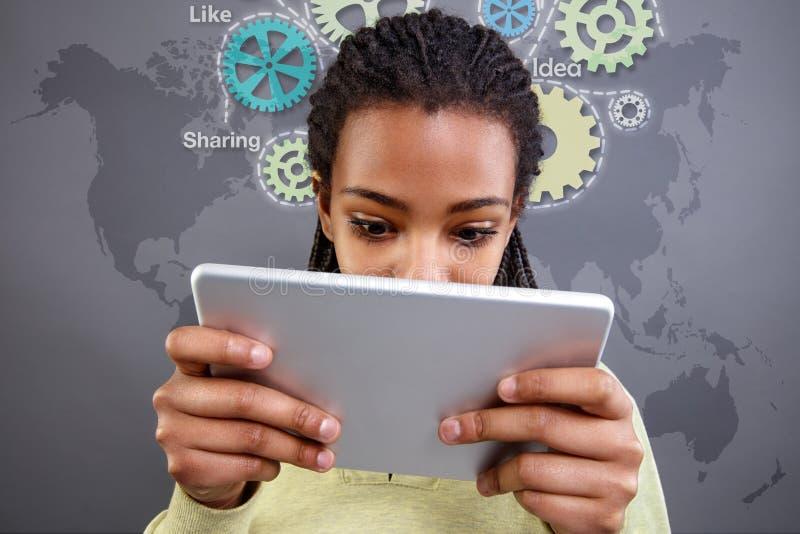 Afrikaans meisje die op tablet kijken stock afbeeldingen