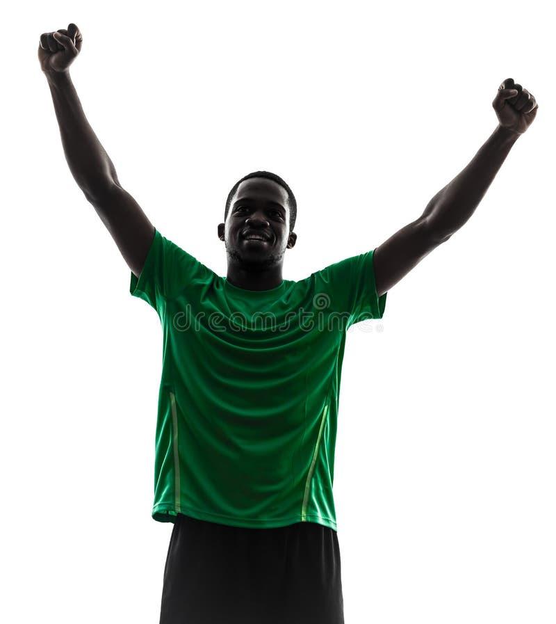 Afrikaans mensenvoetballer het vieren overwinningssilhouet stock foto's