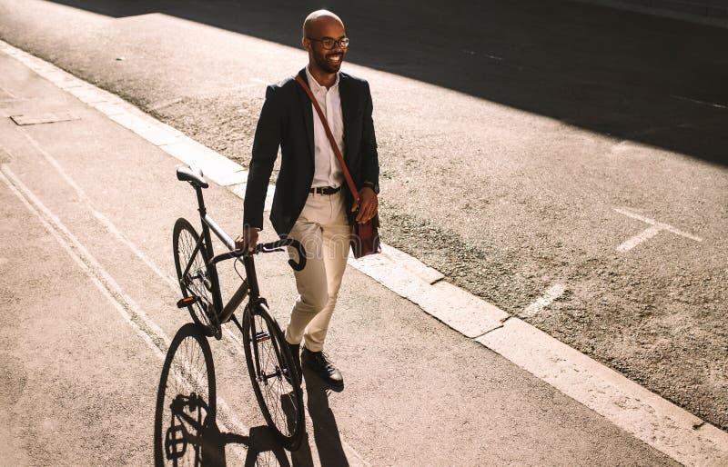 Afrikaans zakenman gaand bureau met zijn fiets royalty-vrije stock afbeelding