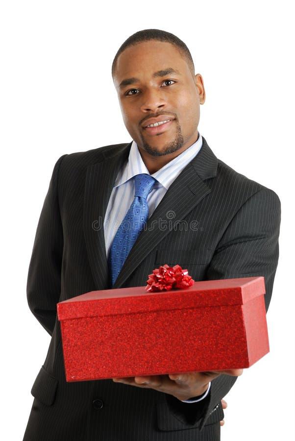 Afrikaanse Amerikaanse bedrijfsmens die een gift houdt stock afbeelding