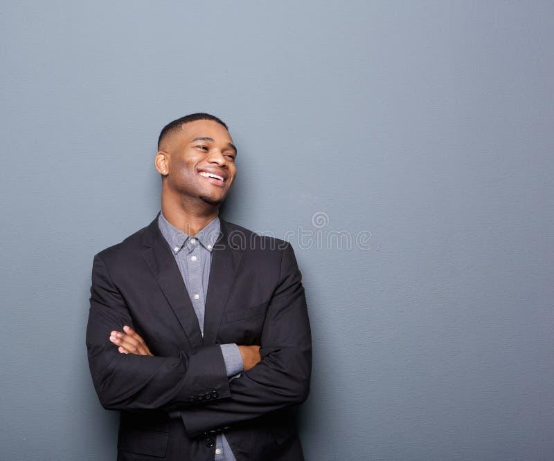 Afrikaanse Amerikaanse bedrijfsmens die met gekruiste wapens glimlachen royalty-vrije stock foto