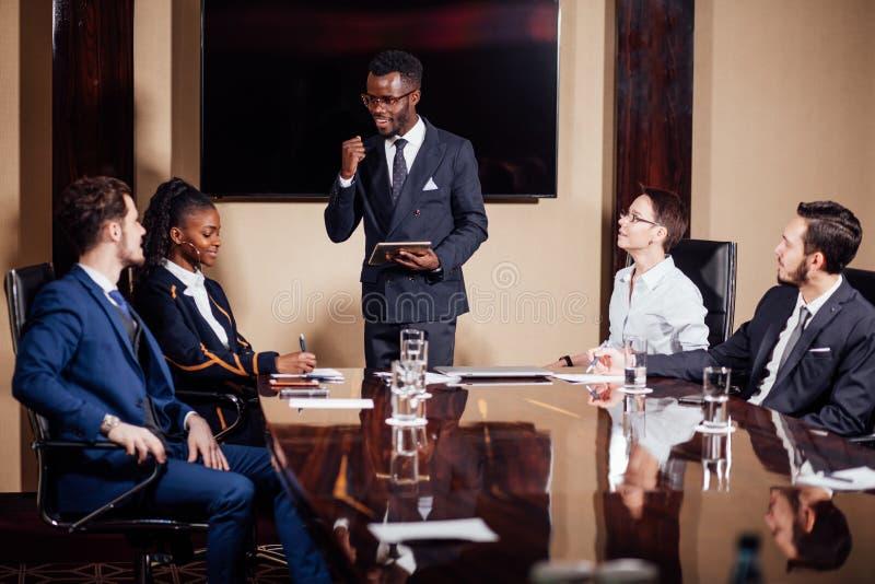 Afrikaanse Amerikaanse bedrijfsmens die presentatie geven aan vennoten royalty-vrije stock afbeelding