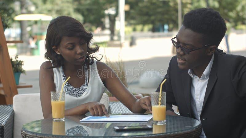 Afrikaanse Amerikaanse bedrijfsmensen die documenten houden, die details verklaren terwijl het hebben van een vergadering bij een royalty-vrije stock fotografie