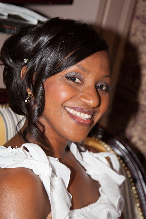 Afrikaanse Amerikaanse bruid die bij de camera glimlachen stock foto