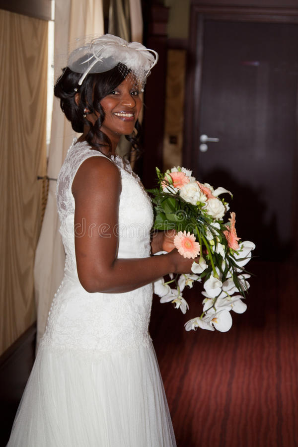 Afrikaanse Amerikaanse bruid die bij het boeket van de cameraholding glimlachen royalty-vrije stock foto