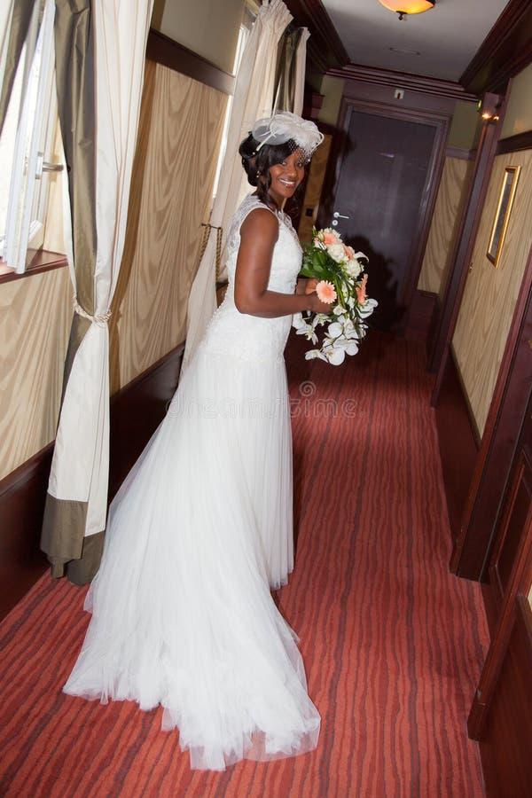Afrikaanse Amerikaanse bruid die bij het boeket van de cameraholding glimlachen stock afbeeldingen