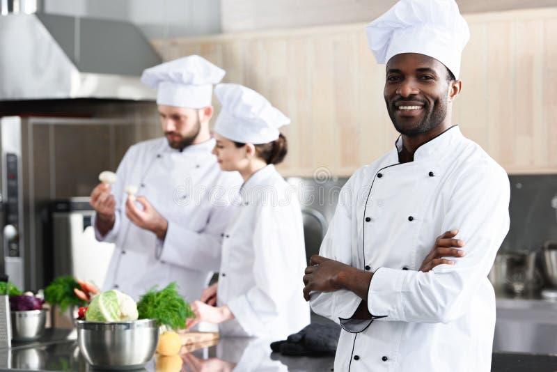 Afrikaanse Amerikaanse chef-kok die zich met gevouwen wapens voor zijn collega's bevinden stock foto