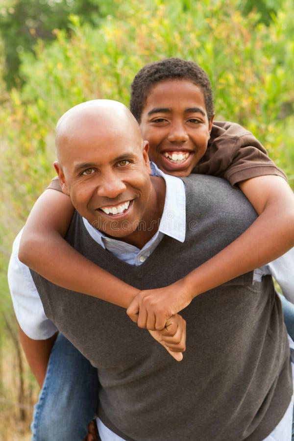 Afrikaanse Amerikaanse en vader en zoon die spreken lachen royalty-vrije stock foto's