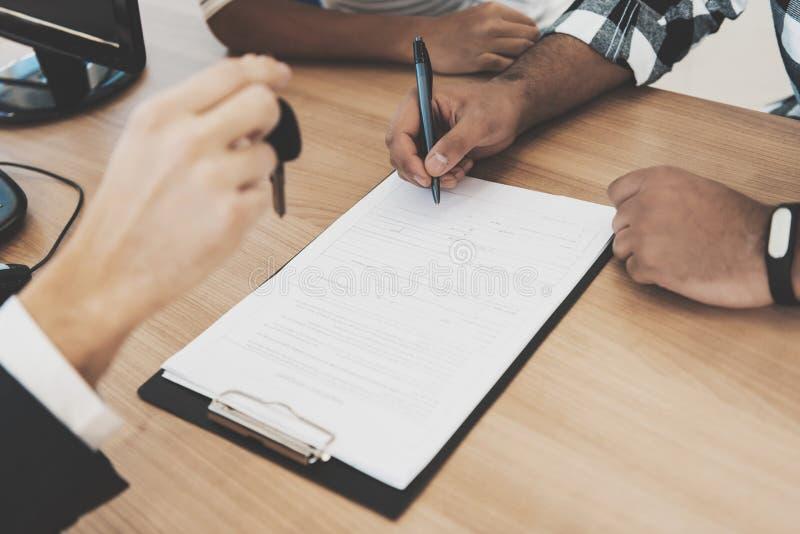 Afrikaanse Amerikaanse familie bij het autohandel drijven De vader ondertekent documenten voor nieuwe auto stock afbeeldingen