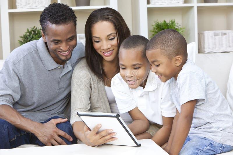 Afrikaanse Amerikaanse Familie die de Computer van de Tablet met behulp van