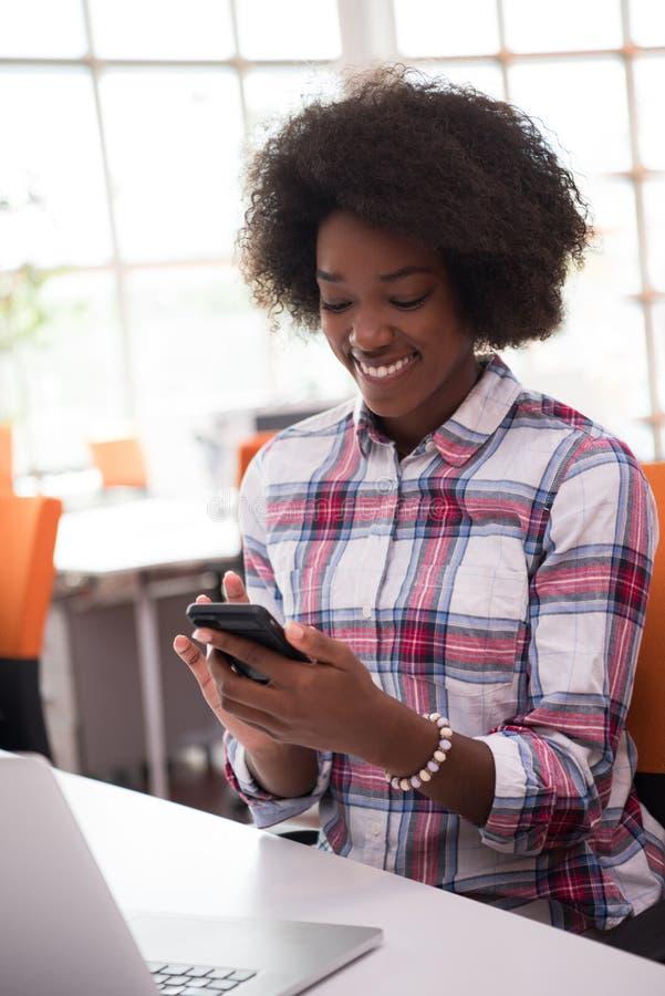 Afrikaanse Amerikaanse informele bedrijfsvrouw die in het bureau werken stock afbeeldingen