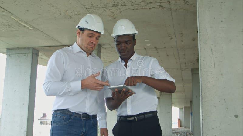 Afrikaanse Amerikaanse ingenieur en caucasinearchitect gebruikend digitale tablet en dragend veiligheidshelmen bij bouwwerf stock foto's