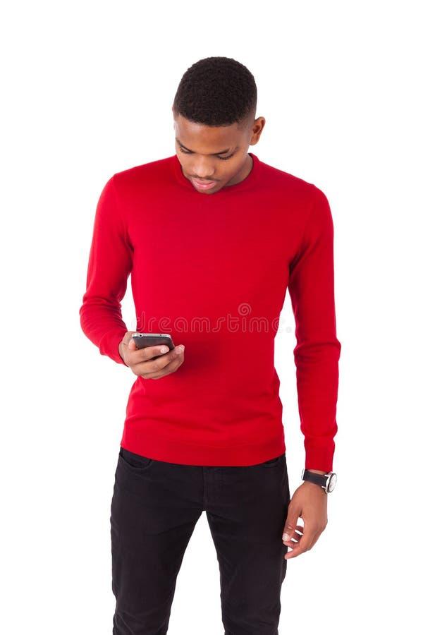 Afrikaanse Amerikaanse jonge mens die een tekstbericht op haar smartph verzenden stock afbeelding