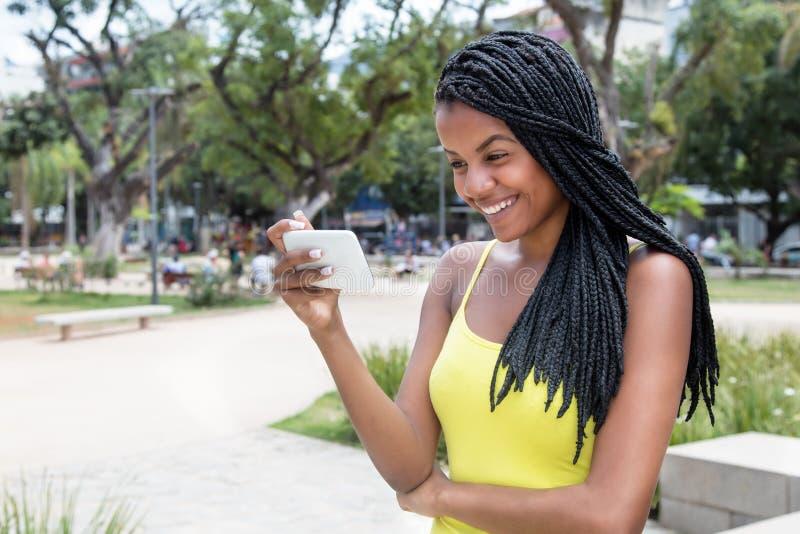 Afrikaanse Amerikaanse jonge volwassen vrouw die op TV met telefoon letten stock foto's