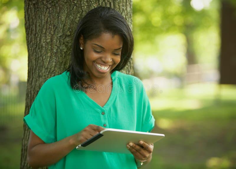 Afrikaanse Amerikaanse jonge vrouw op tabletcomputer royalty-vrije stock afbeelding