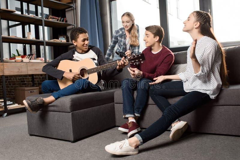 Afrikaanse Amerikaanse jongen die acustic gitaar spelen terwijl zijn en vrienden die thuis luisteren zingen royalty-vrije stock afbeeldingen