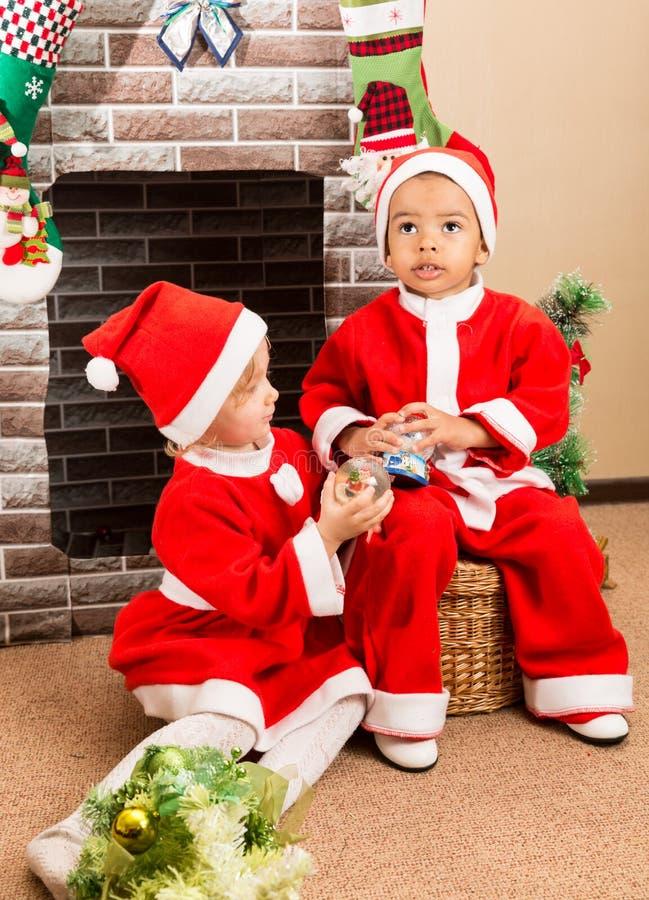 Afrikaanse Amerikaanse jongen en meisje gekleed kostuum Santa Claus door open haard Kerstmis stock afbeeldingen