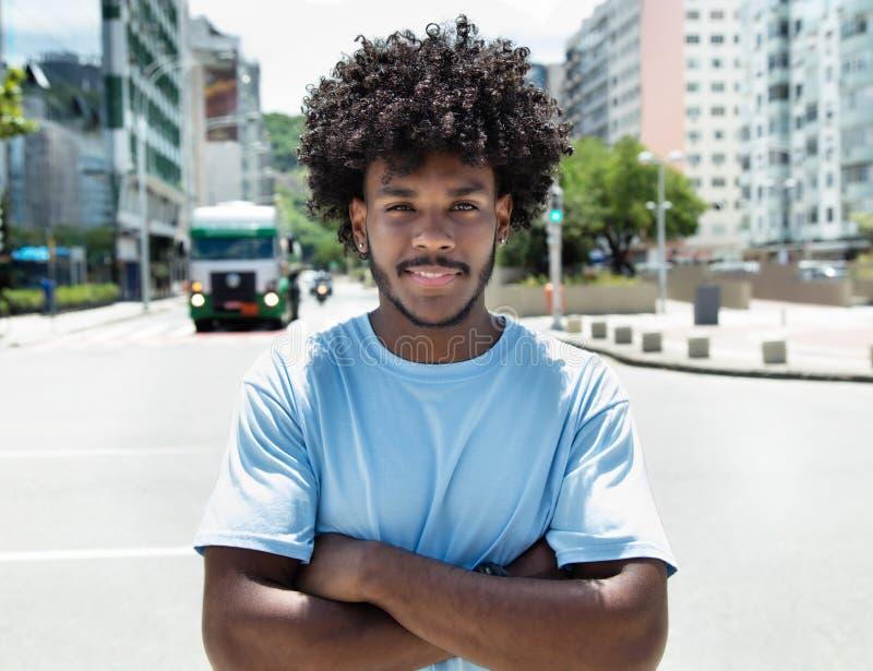 Afrikaanse Amerikaanse kerel met typisch kapsel in stad stock afbeelding